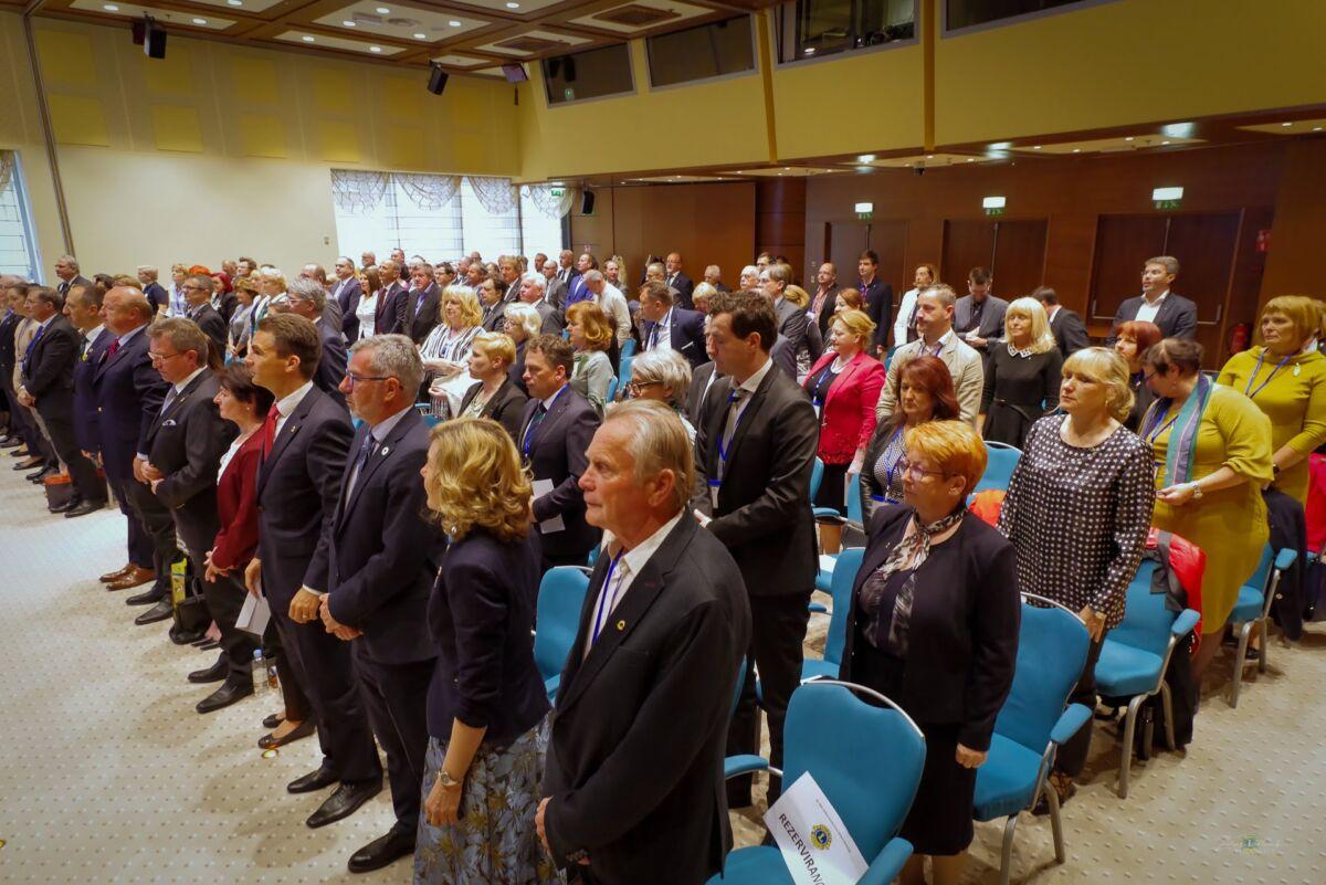 Lions člani na zboru ZLKS D 129 v dvorani stoječ pozdravstojijo ob pozdravu