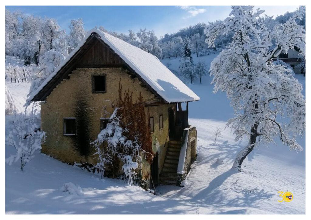 slika stare kmečke hiše v snežni pokrajini