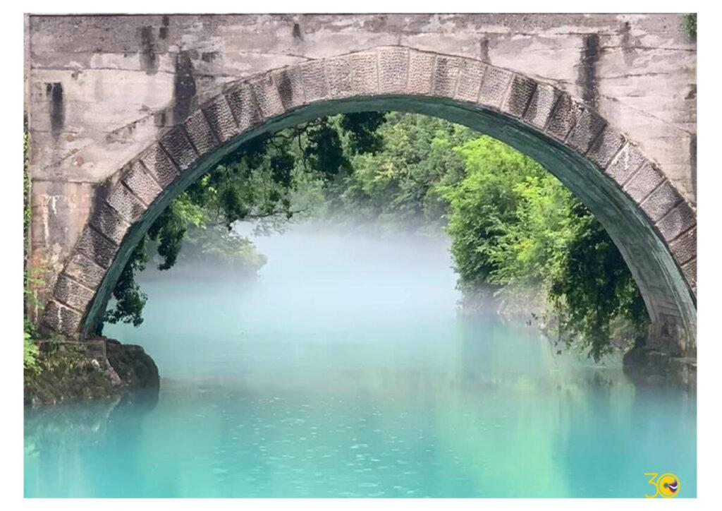 Fotografija zidanega mostu nad modro reku in meglico