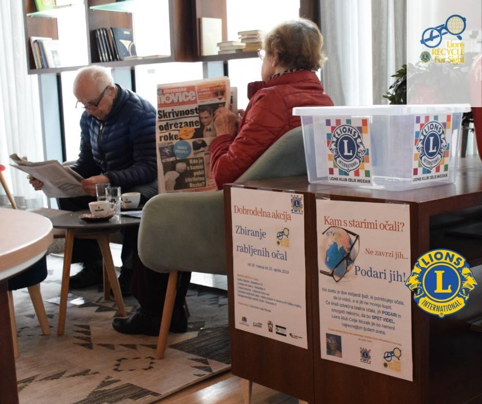 zbirno mesto s škatlo za rabljena očala, na stolih sedita dva strajša, ki bereta