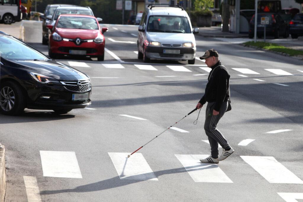 človek z belo palico gre preko ceste po zebri